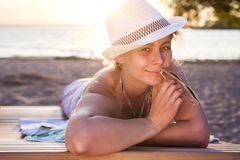 Cute beautiful attractive tanned lady in hat lies on deckchair on sea beach at sunset on warm summer evening. Pretty woman smiles Royalty Free Stock Photography