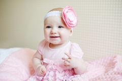 Cute beautiful baby girl sitting on a bed in pink dress and smiling Stock Photos