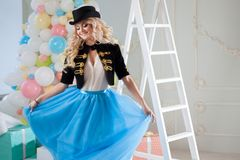 Cute and beautiful blonde dances in a fabulous interior. Charming young woman in a curvy blue skirt. Stock Images