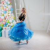 Cute and beautiful blonde in a fabulous interior. Charming young woman in a curvy blue skirt. Royalty Free Stock Photos