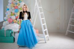 Cute and beautiful blonde in a fabulous interior. Charming young woman in a curvy blue skirt. Stock Photos