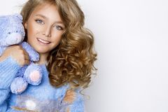 Cute, beautiful blonde young girl with amazing hair, holding teddy bear Stock Photo