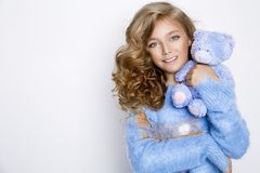 Cute, beautiful blonde young girl with amazing hair, holding teddy bear . Beauty, and joyful girl Royalty Free Stock Photos