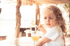 Cute beautiful child girl enjoy drinking fresh juice in hot summer day looking into the distance during summer beach holidays with. Copy space royalty free stock photography