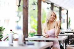 Cute beautiful girl. Sitting at a table in the restaurant and flirts with you stock images