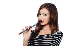 Cute beautiful girl artist Brush teeth bit into the paint in the process draws inspiration. White background, isolated. Stock Photography