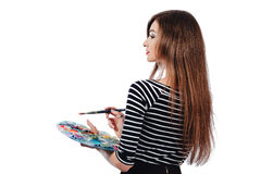 Cute beautiful girl artist holding a palette and brush in the process draws inspiration. White background, isolated. royalty free stock images