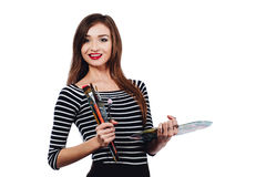Cute beautiful girl artist holding a palette and brush in the process draws inspiration. White background, isolated. Royalty Free Stock Photos
