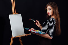 Cute beautiful girl artist painting a picture on canvas an easel. Space for text. Studio black background. Royalty Free Stock Photography