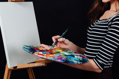 Cute beautiful girl artist painting a picture on canvas an easel. Space for text. Studio black background. Stock Images