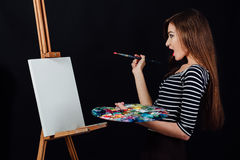 Cute beautiful girl artist painting a picture on canvas an easel. Space for text. Studio black background. Royalty Free Stock Images