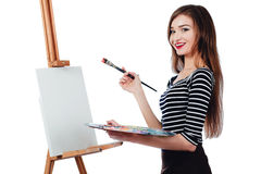 Cute beautiful girl artist painting a picture on  canvas  easel. Space for text. Studio white background, isolated. Royalty Free Stock Image