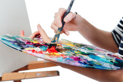 Cute beautiful girl artist painting a picture on  canvas  easel. Space for text. Studio white background, isolated. Stock Photo