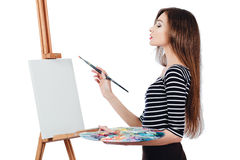 Cute beautiful girl artist painting a picture on  canvas  easel. Space for text. Studio white background, isolated. Royalty Free Stock Images