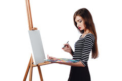 Cute beautiful girl artist painting a picture on  canvas  easel. Space for text. Studio white background, isolated. Cute beautiful girl artist painting a Royalty Free Stock Images