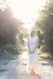 Cute beautiful girl blonde curly hair walking in the woods in a wedding dress in the sun at sunset Royalty Free Stock Photo