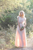 Cute beautiful girl blonde curly hair walking in the woods in a wedding dress in the sun at sunset Royalty Free Stock Images