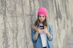 Cute beautiful girl in casual clothes standing near wall on the street and using her smartphone for communication throught the int royalty free stock images