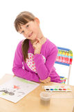 Cute beautiful girl draws paint sitting at the Royalty Free Stock Image