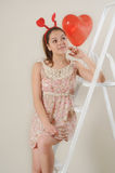 Cute beautiful girl dreaming about Valentine's day on stairs Royalty Free Stock Image