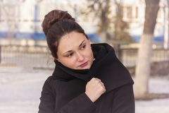 The girl is wrapped in a coat. Cute and beautiful girl wrapped in a coat from the cold stock images
