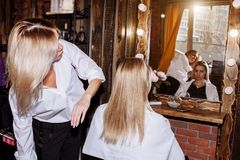 Beautiful blonde attractive woman at hairdresser royalty free stock photography
