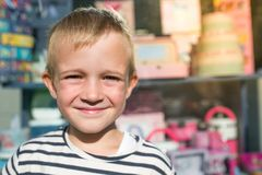 Cute beautiful happy little boy smiling in front of shop-window, looking at camera Royalty Free Stock Images