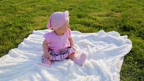 Cute beautiful infant girl in pink clothes sits on white blanket laid on green grass in city park. High-angle shot, close-up cute beautiful infant girl in pink stock video footage