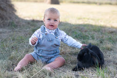 Cute beautiful laughing teen girl on grass with white. And black baby rabbit. Selective focus Stock Image