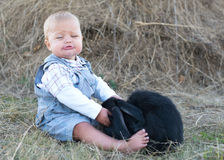 Cute beautiful laughing teen girl on grass with white. And black baby rabbit. Selective focus Stock Photo