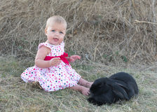 Cute beautiful laughing teen girl on grass with white. And black baby rabbit. Selective focus Royalty Free Stock Images