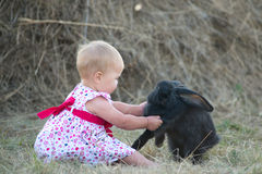 Cute beautiful laughing teen girl on grass with white. And black baby rabbit. Selective focus Stock Images