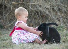 Cute beautiful laughing teen girl on grass with white. And black baby rabbit. Selective focus Royalty Free Stock Photos