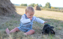 Cute beautiful laughing teen girl on grass with white. And black baby rabbit. Selective focus Stock Photography