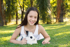 Cute beautiful laughing teen girl with white- black baby rabbit Royalty Free Stock Images