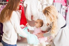Girls out shopping for clothes. Cute beautiful little girl with her mother buying dress in shop Stock Photography