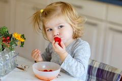 Cute beautiful little toddler girl eating fresh raspberries. Adorable baby child tasting raspberry. Healthy food. Childhood and development. Happy kid at home stock photo