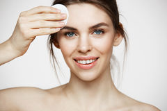 Cute beautiful natural brunette girl cleaning face with cotton sponge smiling looking at camera over white background stock photography