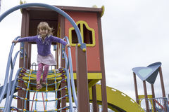 Cute beautiful smiling little girl on a playground. Against the gray sky Royalty Free Stock Photography