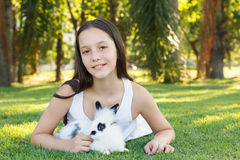 Cute beautiful smiling teen girl on grass with white and black r Royalty Free Stock Images
