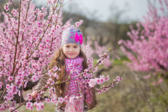 Cute beautiful stylish dressed blond girl standing on a field of spring young peach tree with pink flowers.smiling girl stock photography