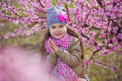 Cute beautiful stylish dressed blond girl standing on a field of spring young peach tree with pink flowers.smiling girl stock images