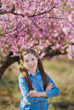 Cute beautiful stylish dressed brunette and blond girls sisters standing on a field of spring young peach tree with pink. Flowers.Lady dressed in jeans in Royalty Free Stock Photo