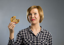 Cute beautiful woman with chocolate stain in mouth eating big delicious cookie Stock Photos