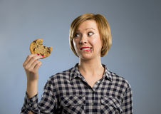 Cute beautiful woman with chocolate stain in mouth eating big delicious cookie Stock Images
