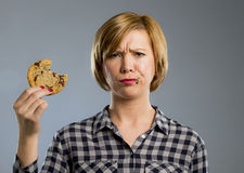 Cute beautiful woman with chocolate stain in mouth eating big delicious cookie Royalty Free Stock Image