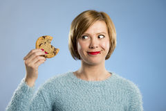 Cute beautiful woman with chocolate stain in mouth eating big delicious cookie Royalty Free Stock Photos