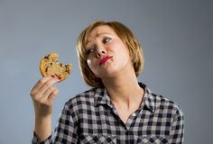 Cute beautiful woman with chocolate stain in mouth eating big delicious cookie Stock Photo