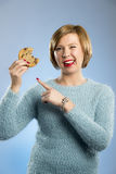 Cute beautiful woman with chocolate stain in mouth eating big delicious cookie Royalty Free Stock Images