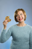Cute beautiful woman with chocolate stain in mouth eating big delicious cookie Stock Image